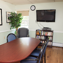 Small private meeting room with large table, TV and books at 60 West in Rocky Hill, CT